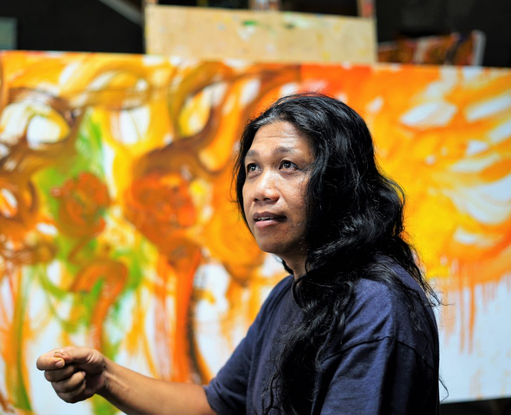 The artist Nanang Lugonto in his studio paints work of art to discover on www.my-obe.com